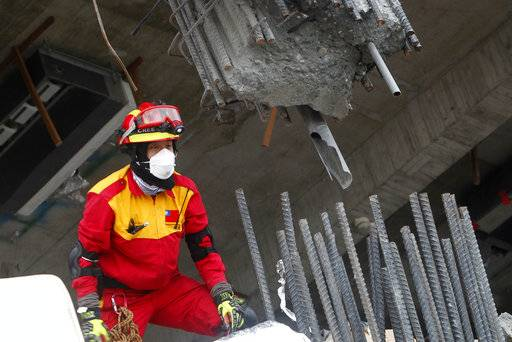 A rescuer looks at a broken pillar during a search operation at an apartment building collapsed after a strong earthquake in Hualien County, eastern Taiwan, Thursday, Feb. 8, 2018. A magnitude 6.4 earthquake struck late Tuesday night caused several buildings to cave in and tilt dangerously. (AP Photo/Chiang Ying-ying