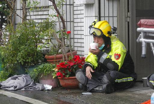A rescuer takes a rest as searches continue for missing people in a collapsed apartment building following a strong earthquake in Hualien County, eastern Taiwan, Thursday, Feb. 8, 2018. A magnitude 6.4 earthquake struck late Tuesday night caused several buildings to cave in and tilt dangerously.
