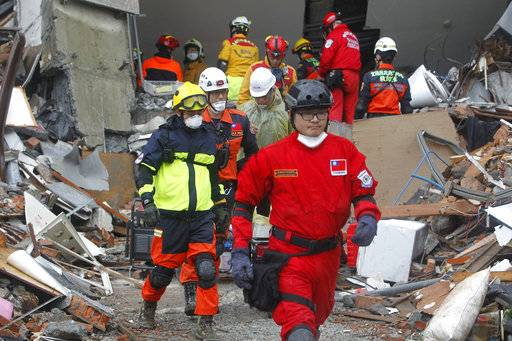 Rescuers continue to search a collapsed apartment building following a strong earthquake in Hualien County, eastern Taiwan, Thursday, Feb. 8, 2018. A magnitude 6.4 earthquake struck late Tuesday night caused several buildings to cave in and tilt dangerously.
