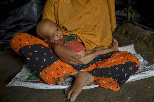 FILE - In this Friday, Oct. 20, 2017, file photo, Noor Aysha, a pregnant Rohingya Muslim woman who crossed over from Myanmar into Bangladesh, holds her 10-month-old son Anamul Hassan, inside her shelter in the Thaingkhali refugee camp, Bangladesh.
