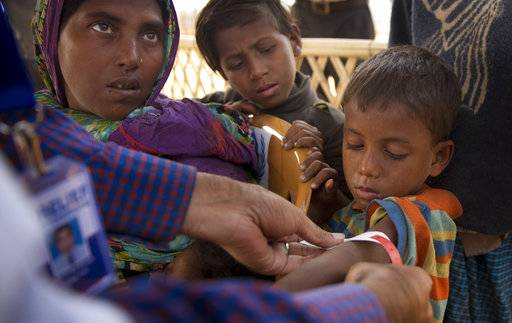 "In this Sunday, Jan. 14, 2018, photo, a volunteer measures the arm of a newly arrived Rohingya boy to check for malnutrition accompanied by his mother and brother upon their arrival at the Balukhali refugee camp near Cox's Bazar, Bangladesh. The lack of food the Rohingya faced at home is evident when they come to the Bangladesh camps, where new refugees, especially children and women, suffer from ""unbelievable� levels of malnutrition, according to Dr. Ismail Mehr."