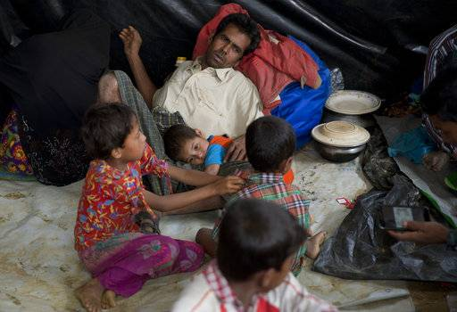 In this Saturday, Jan. 13, 2018, photo, a newly arrived Rohingya family rests together in a transit camp in the Nayaprar refugee camp near Cox's Bazar, Bangladesh. Rohingya Muslims, who have been loathed by Myanmar's Buddhist majority for decades, are locked down in their villages _ sometimes even in their homes _ and prevented from farming, fishing, foraging, trade and work. The Myanmar government denies ethnic cleansing and says it is battling terrorists.