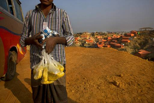 In this Wednesday, Jan. 17, 2018, photo, a newly arrived Rohingya refugee Muslim carries high power protein biscuits and Khicdhi, made from rice and lentils, for his family after arriving at Balukhali refugee camp near Cox's Bazar, Bangladesh. Rohingya Muslims, who have been loathed by Myanmar's Buddhist majority for decades, are locked down in their villages _ sometimes even in their homes _ and prevented from farming, fishing, foraging, trade and work. The Myanmar government denies ethnic cleansing and says it is battling terrorists.