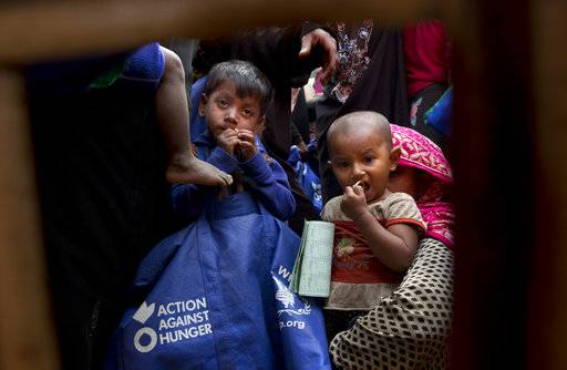 In this Monday, Jan. 15, 2018, photo, Rohingya refugee Muslim children and their mothers wait for their turn to receive food packets from the World Food Program at the Balukhali refugee camp near Cox's Bazar, Bangladesh. In a report released in February 2018, Amnesty International detailed evidence of forced starvation and other abuses by the military that have driven hundreds out of Myanmar in recent weeks.