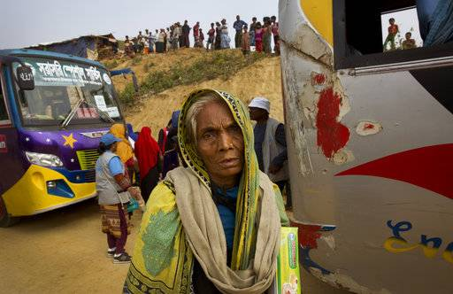 In this Sunday, Jan. 14, 2018, photo, an elderly Rohingya refugee woman arrives with others at a transit camp in Kutupalong refugee camp near Cox's Bazar, Bangladesh. Massacres, rapes and the wholesale destruction of villages by the Myanmar military in western Rakhine state have forced nearly 700,000 Rohingya Muslims to flee to Bangladesh, in reprisal for Rohingya militant attacks on Aug. 25.