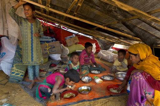 In this Saturday, Jan. 13, 2018, photo, a newly arrived Rohingya family eats at the Balukhali refugee camp near Cox's Bazar, Bangladesh. Rohingya Muslims, who have been loathed by Myanmar's Buddhist majority for decades, are locked down in their villages _ sometimes even in their homes _ and prevented from farming, fishing, foraging, trade and work. The Myanmar government denies ethnic cleansing and says it is battling terrorist