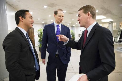 From left, Rep. Joaquin Castro, D-Texas, Sen. Ron Wyden, D-Ore., and Sen. Michael Bennet, D-Colo., chat as they pass in the Senate subway on Capitol Hill in Washington, Wednesday, Feb. 7, 2018.