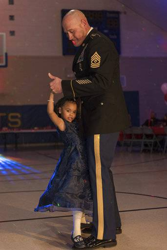 In this photo provided by the Illinois National Guard/U.S. Army, Cayleigh Hinton, daughter of Army Sgt. Terrence Hinton, dances with 1st Sgt. Joseph Bierbrodt of Sheridan, Ill., with the 933rd Military Police Company, at a father-daughter dance held at the Our Lady of Humility School, Wednesday, Feb. 7, 2018, in Beach Park, Ill. Cayleigh's father, Army Sgt. Terrence Hinton, died in a training accident May 14, 2017, in Hawaii. (Staff Sgt. Robert R. Adams/Illinois National Guard/U.S. Army via AP)