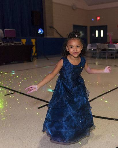 In this photo provided by the Illinois National Guard/U.S. Army, Cayleigh Hinton, daughter of Army Sgt. Terrence Hinton, dances at a father-daughter dance held at the Our Lady of Humility School, Wednesday, Feb. 7, 2018, in Beach Park, Ill. Cayleigh was escorted to the dance by 1st Sgt. Joseph Bierbrodt of Sheridan, Ill., with the 933rd Military Police Company based in Fort Sheridan. Cayleigh's father, Army Sgt. Terrence Hinton, died in a training accident May 14, 2017, in Hawaii. (Staff Sgt. Robert R. Adams/Illinois National Guard/U.S. Army via AP)
