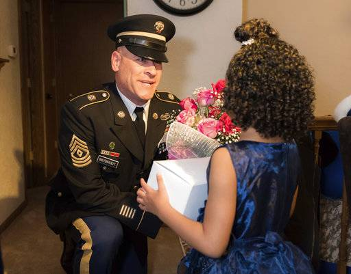 In this photo provided by the Illinois National Guard/U.S. Army, 1st Sgt. Joseph Bierbrodt of Sheridan, Ill., with the 933rd Military Police Company, asks Cayleigh Hinton if he can escort her to the father-daughter dance at the Our Lady of Humility School, Wednesday, Feb. 7, 2018, in Beach Park, Ill. Cayleigh's father, Army Sgt. Terrence Hinton, died in a training accident May 14, 2017, in Hawaii. Beirbrodt along with Cayleigh and her family were taken to the dance in a limousine escorted by the Patriot Guard, multiple nearby police departments and fire departments. (Staff Sgt. Robert R. Adams/Illinois National Guard/U.S. Army via AP)