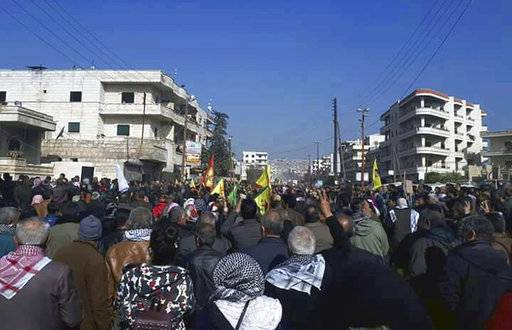 This photo released by the press office of the Kurdish militia, People's Protection Units or YPG, shows protesters holding flags of the YPG and Kurdish parties, during a demonstration against the Turkish assault on Afrin, Aleppo province, north Syria, Tuesday, Feb 6, 2018. The assault is now in its third week. The protesters came from northeastern Syria to show support for Afrin, accusing Turkey of seeking to change the demographics of the predominantly Kurdish enclave, replacing the local population with Arab and Islamist loyalists to Turkish President Recep Tayyip Erdogan. (YPG Press Office via AP)