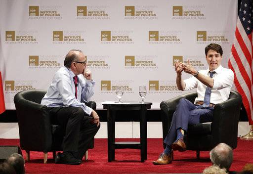 Canadian Prime Minister Justin Trudeau, right, responds to a question from founder and director, David Axelrod, left, at the University of Chicago Institute of Politics Wednesday, Feb. 7, 2018, in Chicago.