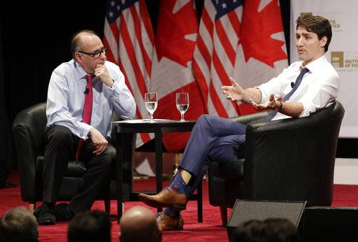 Canadian Prime Minister Justin Trudeau, right, responds to a question from founder and director, David Axelrod, at the University of Chicago Institute of Politics Wednesday, Feb. 7, 2018, in Chicago.