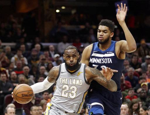 Cleveland Cavaliers' LeBron James, left, drives against Minnesota Timberwolves' Karl-Anthony Towns in the first half of an NBA basketball game, Wednesday, Feb. 7, 2018, in Cleveland.