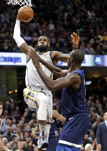 Cleveland Cavaliers' LeBron James, left, drives to the basket against Minnesota Timberwolves' Gorgui Dieng, from Senegal, in the first half of an NBA basketball game, Wednesday, Feb. 7, 2018, in Cleveland.
