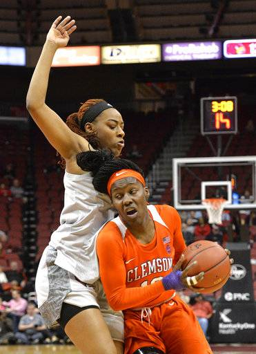 Clemson guard Aliyah Collier (12) attempts to drive around Louisville forward Bionca Dunham during the first half of an NCAA college basketball game Wednesday, Feb. 7, 2018, in Louisville, Ky.