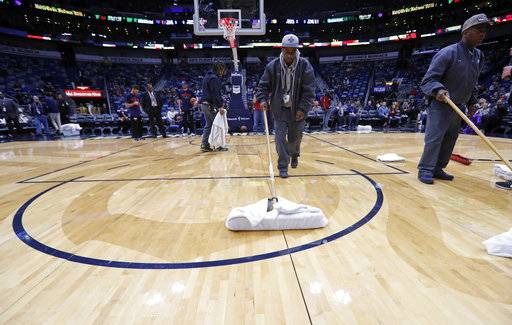 Workers mop the court during a delay for the start of an NBA basketball game against the Indiana Pacers in New Orleans, Wednesday, Feb. 7, 2018. The game was under a delay due to moisture falling from the rafters onto the court.