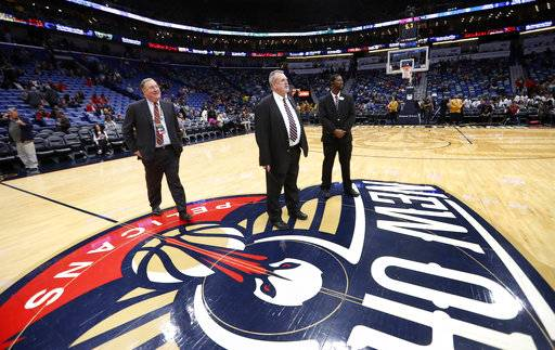 New Orleans Pelicans president Dennis Lauscha, left, walks on the court during a delay for the start of an NBA basketball game against the Indiana Pacers in New Orleans, Wednesday, Feb. 7, 2018. The game was under a delay due to moisture on the court falling from the rafters.