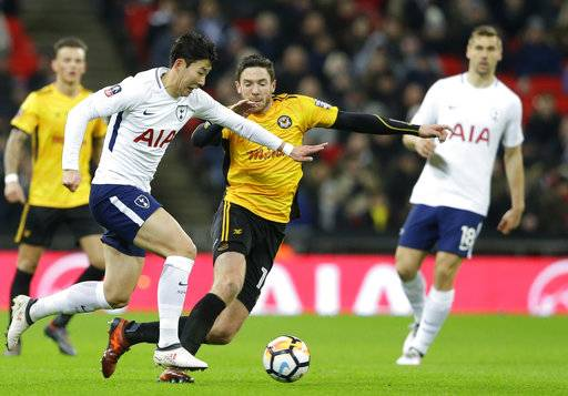 Tottenham's Son Heung-min, left vies for the ball with Newport's Robbie Willmott during the English FA Cup fourth round replay soccer match between Tottenham Hotspur and Newport County at Wembley stadium in London, Wednesday, Feb. 7, 2018.