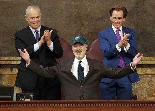 Democratic Gov. Tom Wolf puts on a Philadelphia Eagles hat to celebrate their Super Bowl win before he gives his budget address at the state Capitol in Harrisburg, Pa., on Tuesday, Feb. 6, 2018.