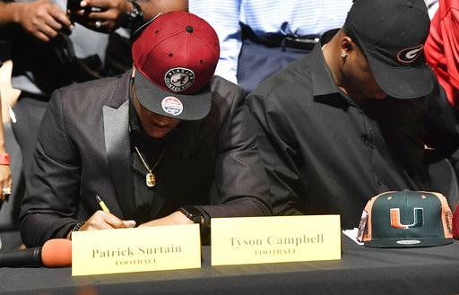 Patrick Surtain Jr., left, and Tyson Campbell, from the football team at American Heritage High School, sign to the University of Alabama and University of Georgia respectively, on national signing day, Wednesday, Feb. 7, 2018, in Plantation, Fla. (Taimy Alvarez/South Florida Sun-Sentinel via AP)