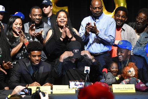 American Heritage High School football players, from left, Patrick Surtain Jr., Tyson Campbell and Nesta Silvera celebrate signing with the University of Alabama, University of Georgia and University of Florida respectively on national signing day, Wednesday, Feb. 7, 2018, in Plantation, Fla. (Taimy Alvarez/South Florida Sun-Sentinel via AP)