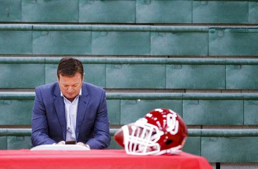 Former University of Oklahoma football coach Bob Stoops uses his cell phone as he waits for his sons, Isaac and Drake Stoops, to announce they will be preferred walk-on for Oklahoma during national signing day at Norman North High School in Norman, Okla., Wednesday, Feb. 7, 2018. (Chris Landsberger/The Oklahoman via AP)