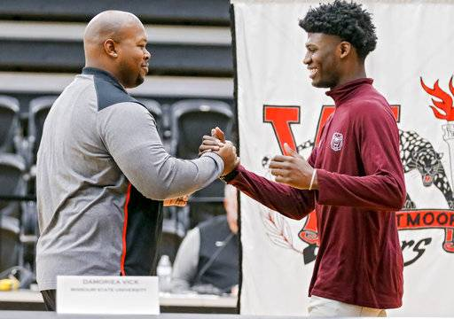 Westmoore High School's Damoriea Vick shakes hands with football coach Lorenzo Williams before he signed his letter of intent to play football for Missouri State University during national signing day in Norman, Okla., Wednesday, Feb. 7, 2018. (Chris Landsberger/The Oklahoman via AP)