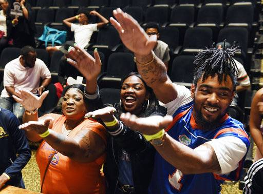 The family of Andrew Chatfield gesture after Chatfield signed with the University of Florida on national signing day in Plantation, Fla., Wednesday, Feb. 7, 2018. From left are Candy Diggs, Tiaunte Diggs and Lamont Green. (Taimy Alvarez/South Florida Sun-Sentinel via AP)