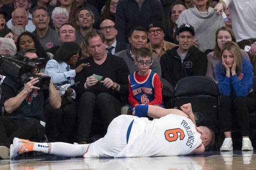 New York Knicks forward Kristaps Porzingis lies on the ground after being injured during the first half of the team's NBA basketball game against the Milwaukee Bucks, Tuesday, Feb. 6, 2018, at Madison Square Garden in New York.