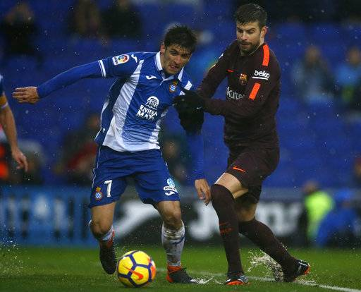 FC Barcelona's Gerard Pique, right, duels for the ball against Espanyol's Gerard Moreno during the Spanish La Liga soccer match between Espanyol and FC Barcelona at RCDE stadium in Cornella Llobregat, Spain, Sunday, Feb. 4, 2018.