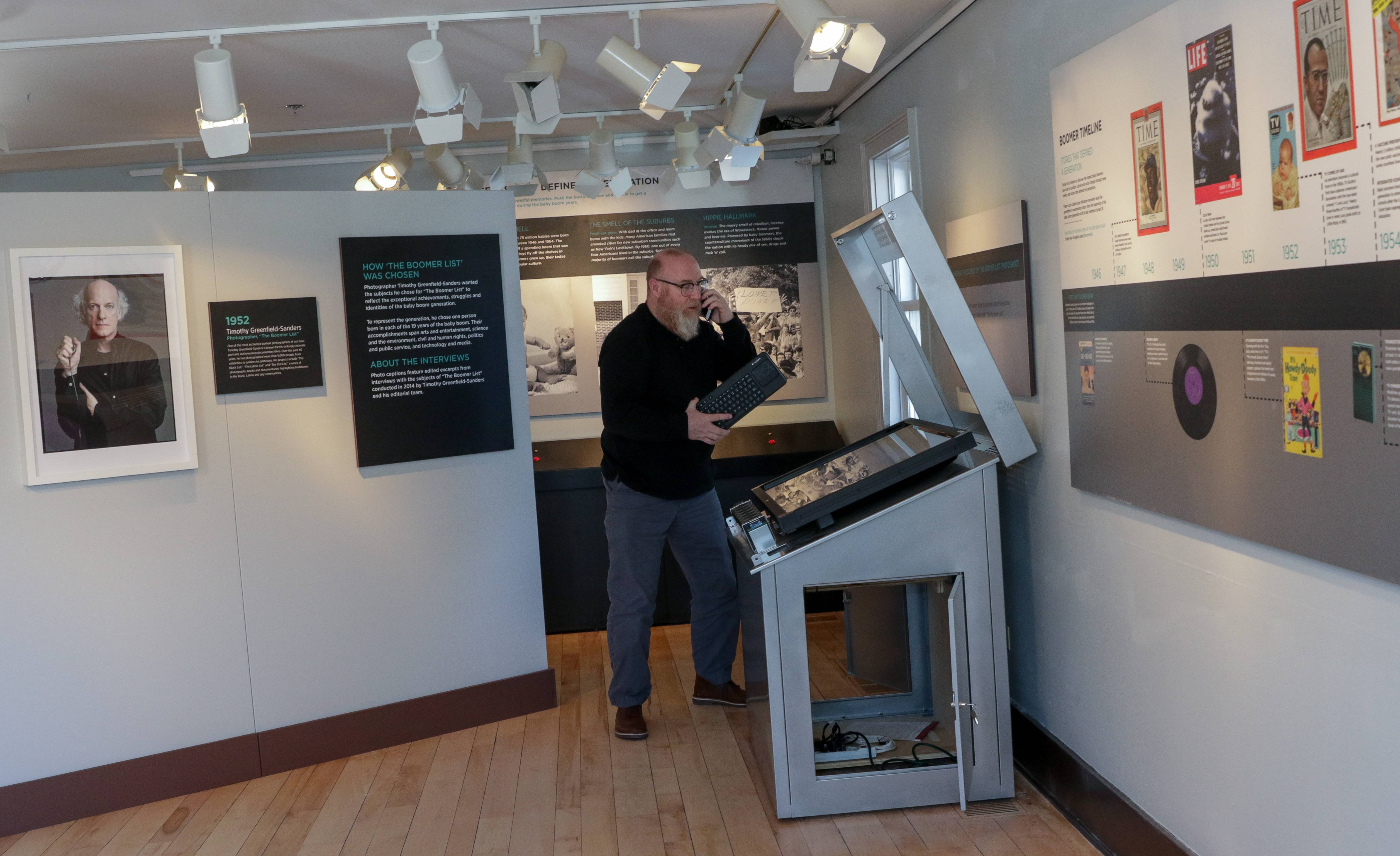"Lance Tawzer, director of innovation and experience, works on a touch screen interactive display for ""The Boomer List,"" a traveling photo exhibit visiting Naper Settlement through mid-March."