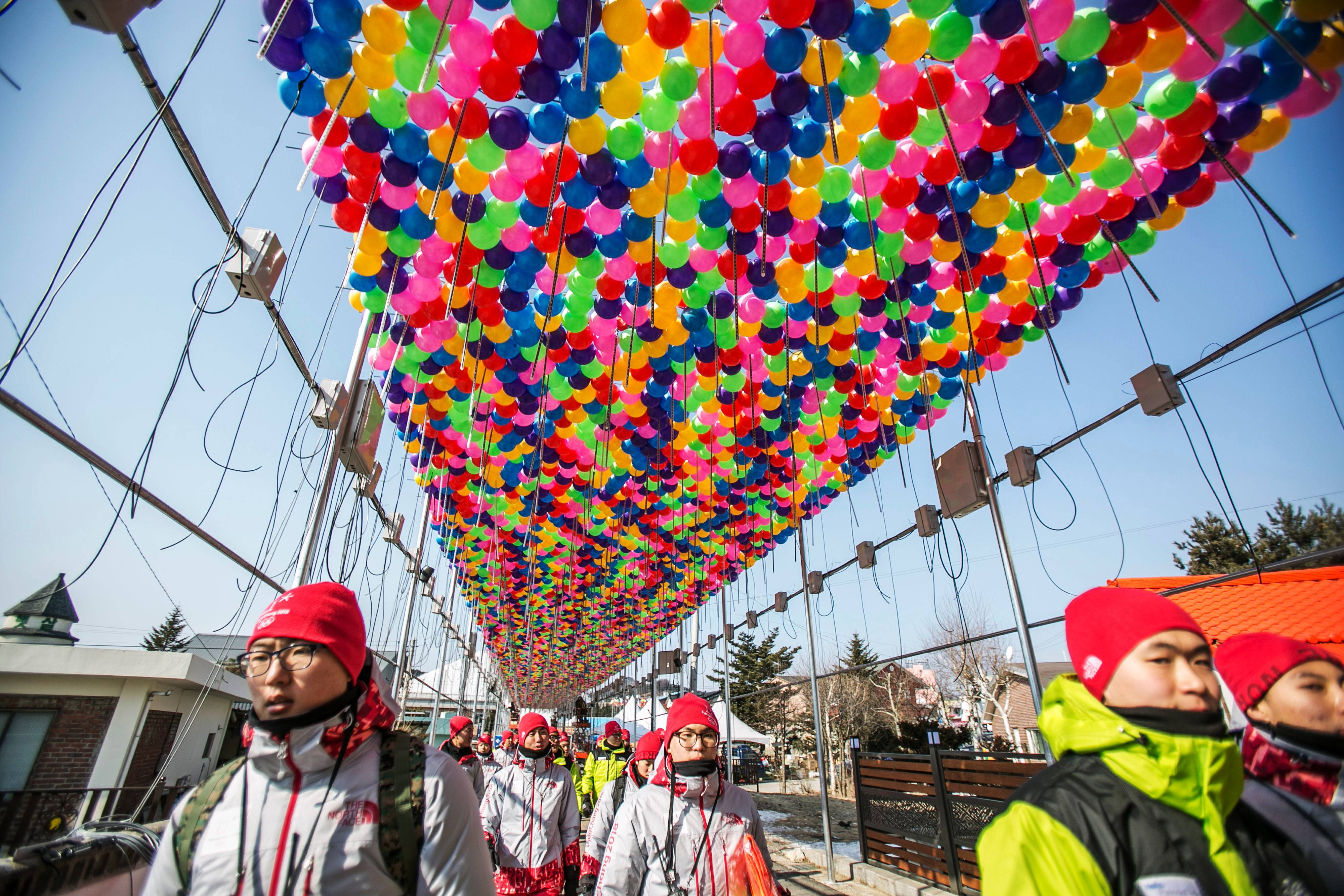 Olympic volunteers walk under balloon decorations ahead of the 2018 Pyeongchang Winter Olympic Games in the Hoenggye-ri village area of Pyeongchang, South Korea, on Feb. 8, 2018. MUST CREDIT: Bloomberg photo by Jean Chung.