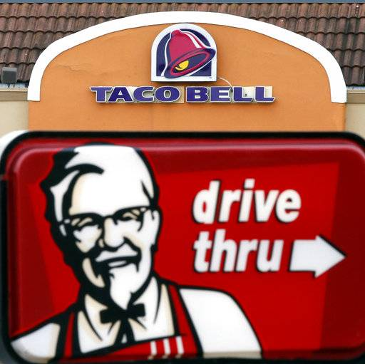 FILE - This Jan. 31, 2014, file photo, shows a Taco Bell facade behind a KFC drive-thru sign in Saugus, Mass.  The owner of KFC and Taco Bell, is teaming up with Grubhub to expand its delivery business. Yum Brands said Thursday, Feb. 8, 2018,  that Grubhub will run KFC and Taco Bell delivery and online ordering in the United States. GrubHub will provide delivery people and its technology.(