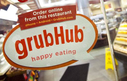 FILE - In this April 4, 2014 file photo, a sign for GrubHub is displayed on the door to a New York restaurant.  The owner of KFC and Taco Bell, is teaming up with Grubhub to expand its delivery business. Yum Brands said Thursday, Feb. 8, 2018,  that Grubhub will run KFC and Taco Bell delivery and online ordering in the United States. GrubHub will provide delivery people and its technology.