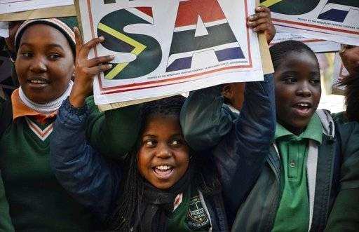 FILE - In this July 19 2012, file photo, young children join hundreds of fans gathered at Johannesburg's O.R. Thambo Airport to bid farewell to the South Africa Olympic team members who were departing for the games in London. The Olympics could be finally heading to Africa, but first there'll be a tiny step to take: hosting the much smaller Youth Olympic Games in 2022.