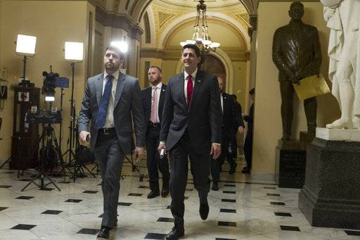House Speaker Paul Ryan of Wis., right, walks to his office at the Capitol, Thursday, Feb. 8, 2018, in Washington., as lawmakers pushed to enact a massive budget deal; along with a stopgap temporary measure to prevent a government shutdown at midnight.