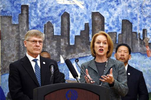 Seattle City Attorney Pete Holmes, left, looks on as Mayor Jenny Durkan speaks at a news conference announcing plans for the city to move to vacate misdemeanor marijuana possession convictions, Thursday, Feb. 8, 2018, in Seattle. City Council member Bruce Harrell looks on at right. Five years after Washington state legalized marijuana, Seattle officials say they're moving to automatically clear past misdemeanor convictions for pot possession. San Francisco recently took the same step.