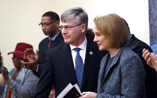 Seattle City Attorney Pete Holmes, left, steps back after speaking as Mayor Jenny Durkan moves to the microphone at a news conference announcing plans for the city to move to vacate misdemeanor marijuana possession convictions, Thursday, Feb. 8, 2018, in Seattle. City Council-member Bruce Harrell looks on at right. Five years after Washington state legalized marijuana, Seattle officials say they're moving to automatically clear past misdemeanor convictions for pot possession. San Francisco recently took the same step.