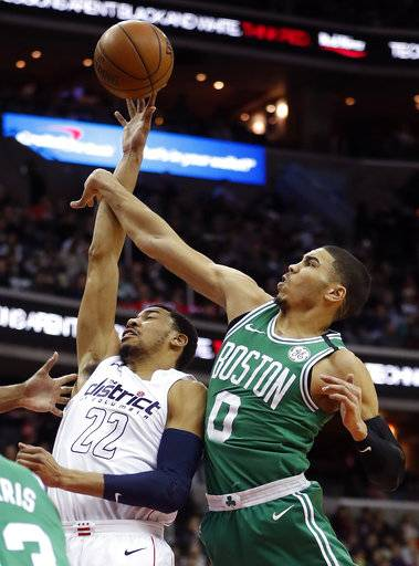 Washington Wizards forward Otto Porter Jr. (22) is fouled by Boston Celtics forward Jayson Tatum (0) during the first half of an NBA basketball game Thursday, Feb. 8, 2018, in Washington.