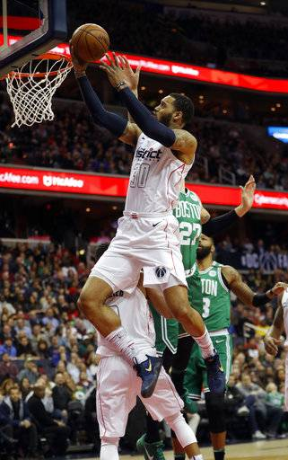 Washington Wizards forward Mike Scott (30) scores past Boston Celtics forward Daniel Theis (27), from Germany, during the first half of an NBA basketball game Thursday, Feb. 8, 2018, in Washington.