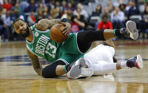 Boston Celtics forward Marcus Morris (13) beats out Washington Wizards forward Kelly Oubre Jr. (12) for the ball during the first half of an NBA basketball game Thursday, Feb. 8, 2018, in Washington.