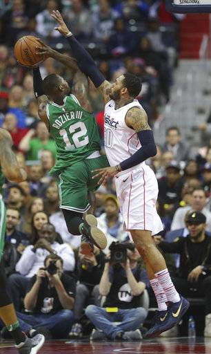 Boston Celtics guard Terry Rozier (12) is fouled while driving to the basket by Washington Wizards forward Mike Scott (30) during the first half of an NBA basketball game Thursday, Feb. 8, 2018, in Washington.