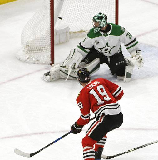 Chicago Blackhawks center Jonathan Toews (19) scores a goal on Dallas Stars goaltender Ben Bishop (30) during the first period of an NHL hockey game Thursday, Feb. 8, 2018, in Chicago.