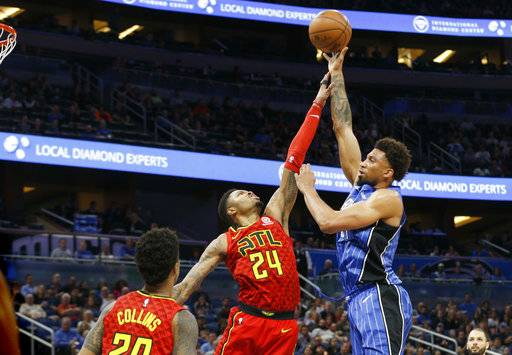Orlando Magic center Khem Birch (24) shoots over Atlanta Hawks guard Kent Bazemore (24) and forward John Collins (20) during the second quarter of an NBA basketball game in Orlando, Fla., on Thursday, Feb. 8, 2018.