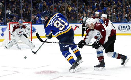 St. Louis Blues' Vladimir Tarasenko, of Russia, takes a shot as Colorado Avalanche goaltender Semyon Varlamov, left, of Russia, and Tyson Barrie (4) defend during the second period of an NHL hockey game Thursday, Feb. 8, 2018, in St. Louis.