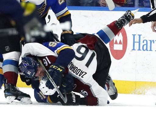 St. Louis Blues' Vladimir Tarasenko (91), of Russia, and Colorado Avalanche's Nikita Zadorov (16), of Russia, fight during the first period of an NHL hockey game Thursday, Feb. 8, 2018, in St. Louis.