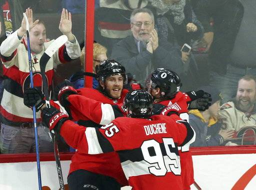 Ottawa Senators' Mike Hoffman (68) celebrates his winning overtime goal against the Nashville Predators with teammates Matt Duchene (95) and Thomas Chabot (72) NHL hockey game action in Ottawa, Ontario, Thursday, Feb. 8, 2018. (Fred Chartrand/The Canadian Press via AP)