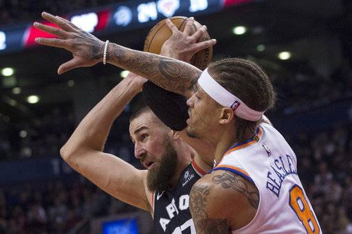 Toronto Raptors Jonas Valanciunas, left, looks to make a pass under pressure from New York Knicks' Michael Beasley during the first half of an NBA basketball game Thursday, Feb. 8, 2018, in Toronto. (Chris Young/The Canadian Press via AP)