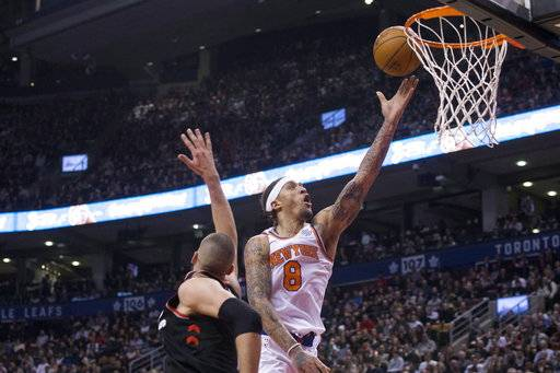 New York Knicks Michael Beasley shoots next to Toronto Raptors' Jonas Valanciunas during the second half of an NBA basketball game Thursday, Feb. 8, 2018, in Toronto. (Chris Young/The Canadian Press via AP)
